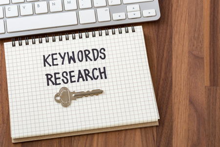 Keywords research words on notebook with key and computer keyboard Stock Photo