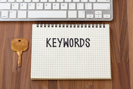 Keywords word on notebook with key on wooden table