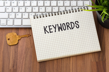 Keywords word on notebook with key and computer on wooden table Stock Photo