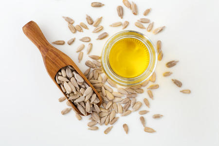 Sunflower oil and sunflower seeds in wood scoop on white background Stock Photo