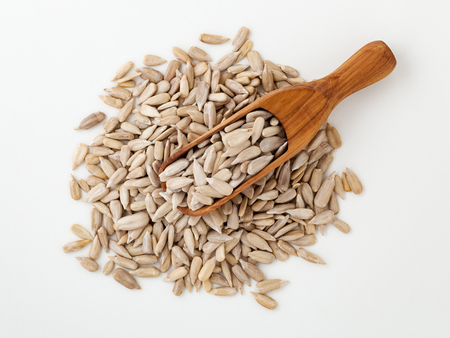 Sunflower seeds in wooden scoop on white background