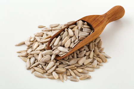 Sunflower seeds in wood scoop on white background Stock Photo