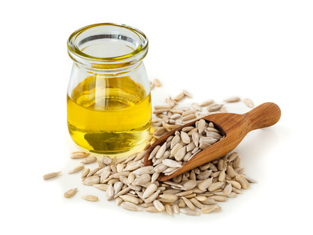 Sunflower oil with sunflower seeds in wood scoop on white background