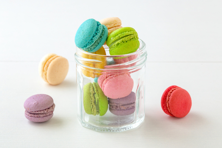 Macaroons in glass bottle on white table