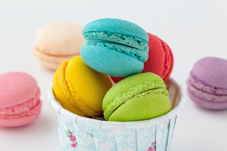 Sweet macaroons in cup closed up on white background