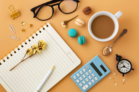 Woman workspace with flowers, macaroons, calculator, notebook, pen, glasses, clock and coffee cup from top view