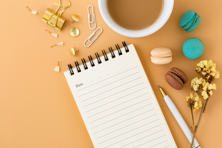 Woman workspace with macaroons, flowers, notebook, pen and coffee cup, flat lay background with space