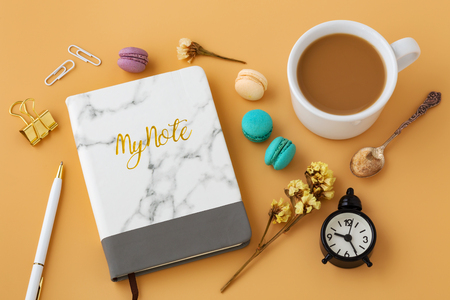 Woman workspace with flowers, macaroon, notebook, pen, coffee cup and vintage spoon Stock Photo