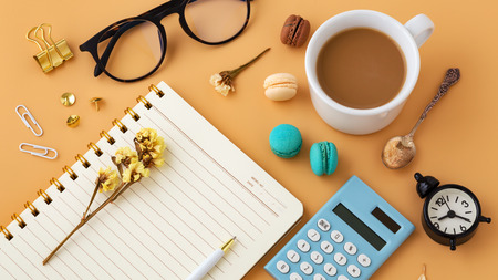 Woman workspace with macaroon, flower, calculator, notebook, glasses and coffee cup