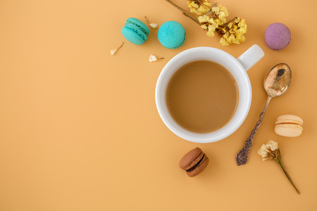 Coffee cup with macaroons, flower and vintage spoon. Flat lay background with space