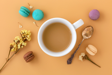 Coffee cup with macaroons, flower and vintage spoon. Flat lay, top view Stock Photo