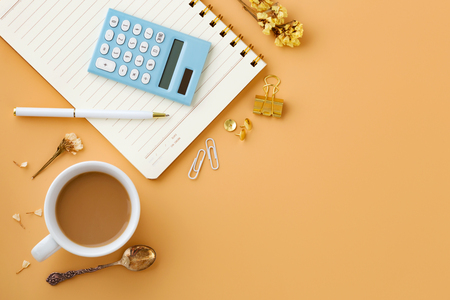 Woman workspace background with calculator, notebook, pen and coffee cup from top view