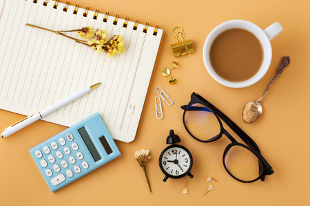 Woman workspace with flowers, calculator, notebook, pen, glasses and coffee cup, flat lay