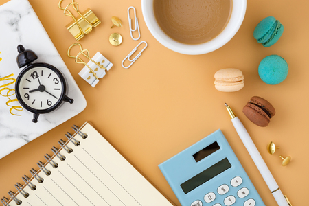 Woman workspace with macaroons, notebook, clock, calculator and coffee cup, flat lay background with space Stock Photo
