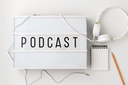 Podcast word on lightbox with headphones, notepad and pencil on white background, podcast concept, flat lay