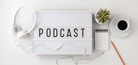 Podcast word on lightbox with headphones, notepad and coffee cup, podcast concept, flat lay