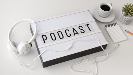 Podcast concept with headphones on white table Stock Photo