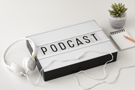 Podcast word on lightbox with headphones and notepad on white background, podcast concept