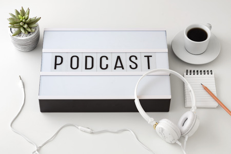 Podcast word on lightbox with headphones, podcast concept