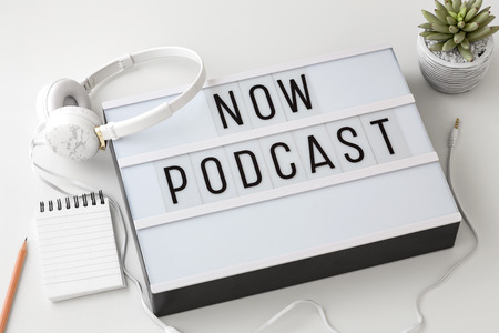 Now Podcast word on lightbox with headphones on white background, podcast concept Stock Photo