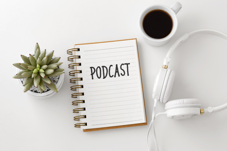 Podcast concept with headphones, notebook and coffee cup on white desk, top view