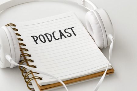 Podcast concept with headphones and podcast word on notebook on white background