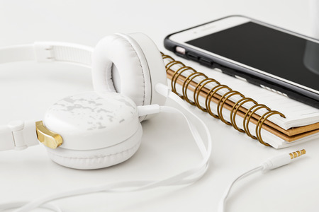 Headphones with smartphone on notebook for podcast concept