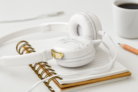 Headphones on notebook on white table with coffee cup Stock Photo