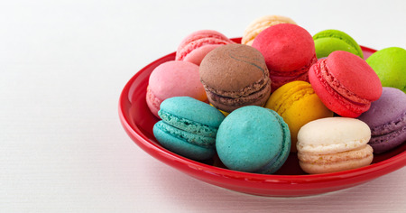 Macaroons on red plate on white table Stock Photo