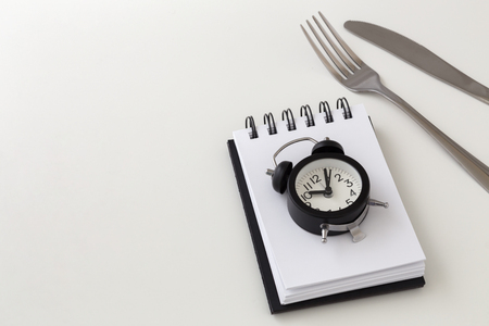 Clock with fork and knife, intermittent fasting and weight loss plan concept
