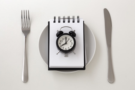 Clock on notepad with fork and knife, intermittent fasting and weight loss plan concept
