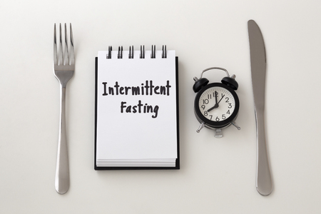 Intermittent fasting word on notepad with clock, fork and knife, weight loss plan Stock Photo