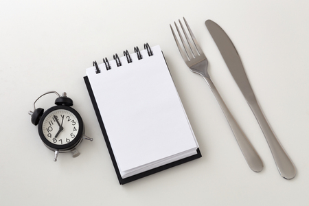 Clock and notepad with fork and knife, intermittent fasting and weight loss plan concept Stock Photo