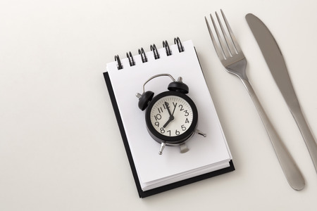 Clock on notepad with fork and knife for intermittent fasting and weight loss plan concept on white background Stock Photo