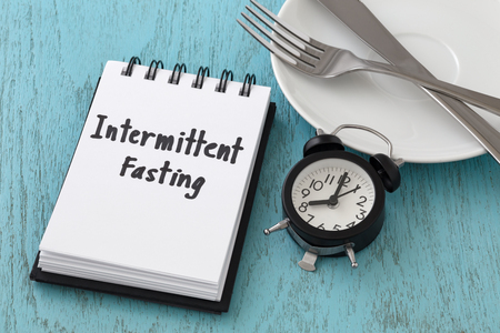 Intermittent fasting word on notepad with clock, fork and knife on white plate, intermittent fasting and weight loss  concept