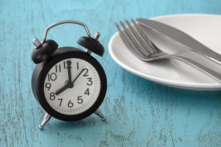 Reloj con tenedor y cuchillo en plato blanco, ayuno intermitente, plan de comidas, concepto de pérdida de peso