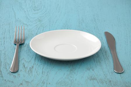 White plate with fork and knife on blue table
