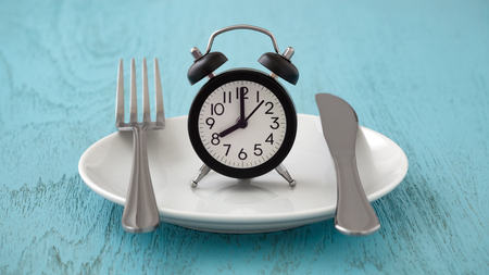 Clock on white plate with fork and knife, intermittent fasting, meal plan, weight loss concept on blue table