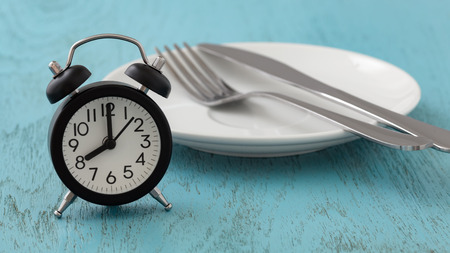 Intermittent fasting concept with clock, white plate, fork and knife on blue table
