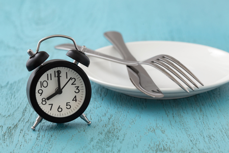 Clock with white plate, fork and knife, intermittent fasting, diet, weight loss concept on blue wooden table Stock Photo