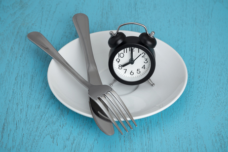 Intermittent fasting concept with clock on white plate, fork and knife on blue table