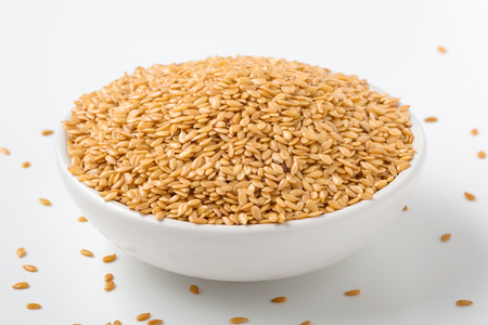 Golden flaxseed in bowl on white background Standard-Bild