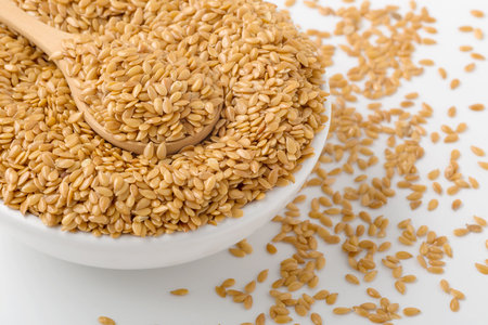 Golden flaxseed in wooden spoon and bowl on white background, closed up