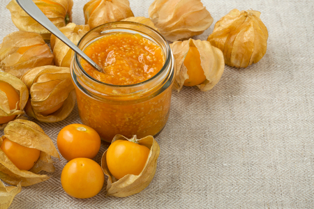 Golden berry jam in jar or cape gooseberries background with space Archivio Fotografico