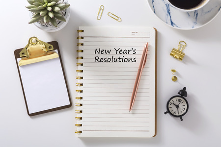 New year resolutions in notebook with pen, clipboard on white desk, flat lay