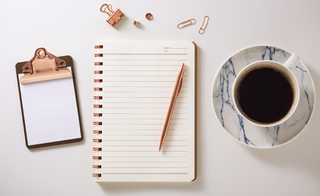 Flat lay desk with notebook, clipboard, coffee cup and pen, rose gold accessories, warm tone