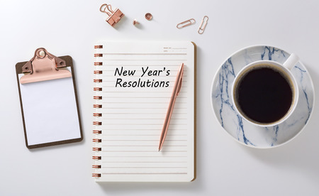 New year resolutions in notebook with rose gold pen, clipboard and coffee cup on white desk, flat lay