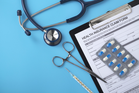 Health insurance form with stethoscope, pills and doctor tools on blue table Stock Photo
