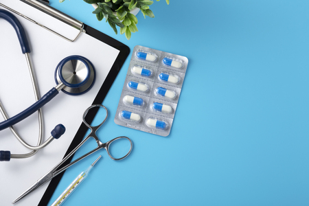 Doctor desk with pills and stethoscope, top view, blue background