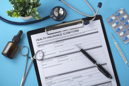 Health insurance form and pen on doctor desk, top view, blue background